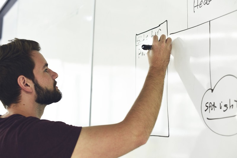 Čovek piše na beloj tabli