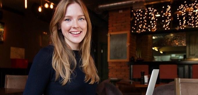 Nasmejana devojka koja radi kao hostesa u restoranu
