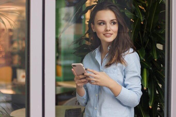 Devojka u plavoj košulji sa telefonom u rukama