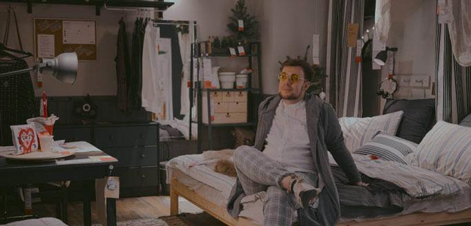 Čovek u pidžami sedi na krevetu u sobi