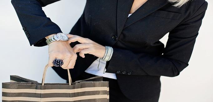 Poslovna žena u crnom sakou pokazuje prstom na ručni sat