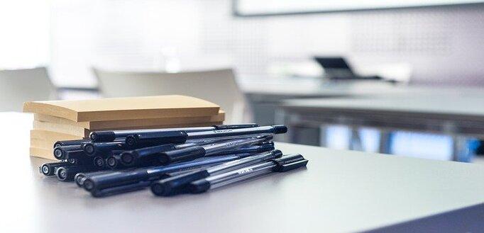 Nekoliko hemijskih olovki i blok papira na kancelarijskom stolu